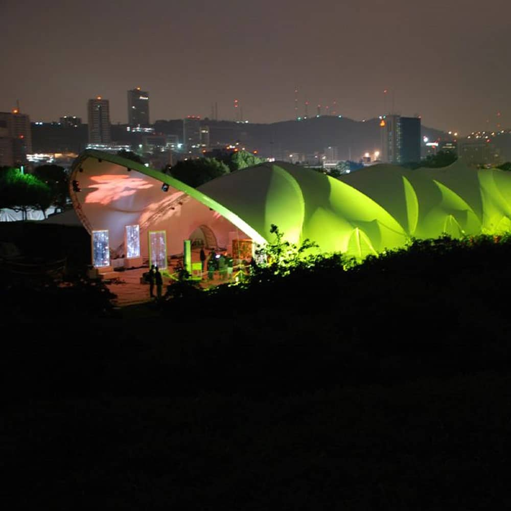 Saddlespan Tent lit at night creates a striking look for any event